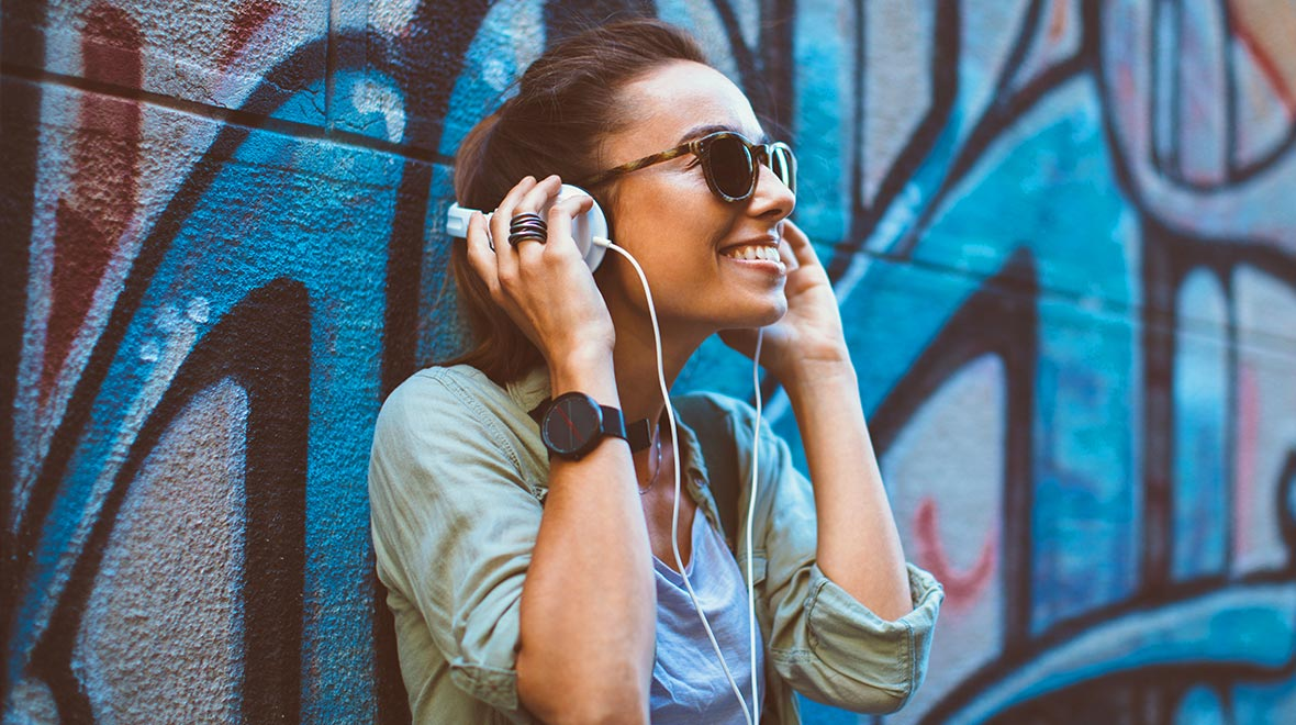 Person listening to a music subscription business service on white headphones