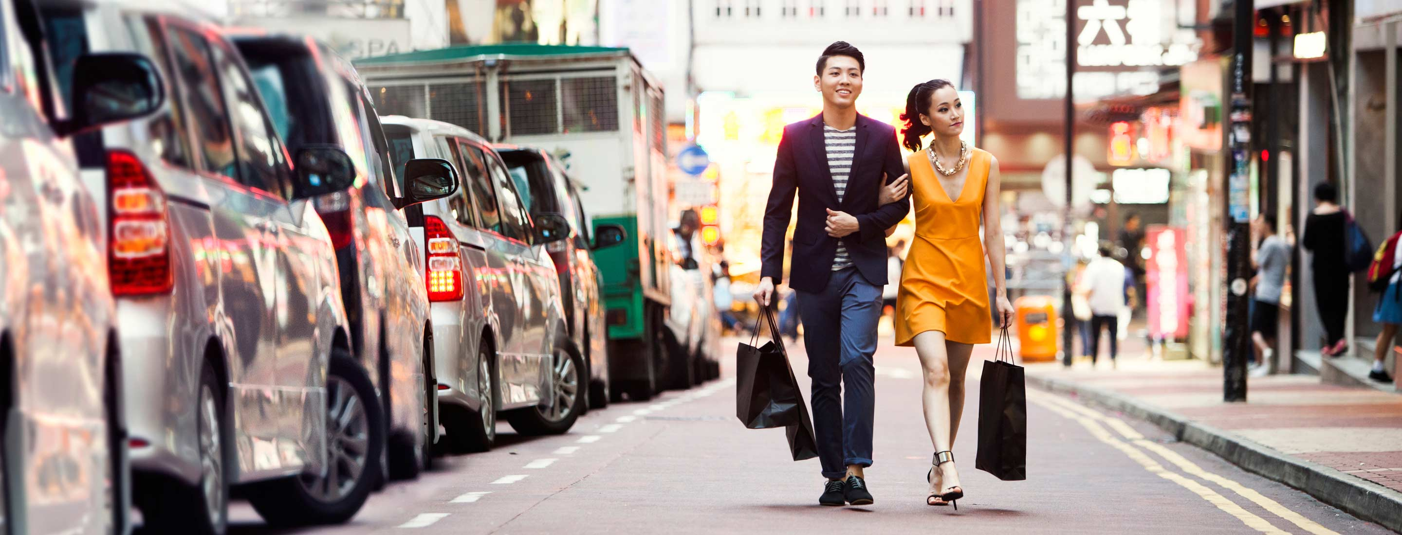 Two people walking down street in Asia